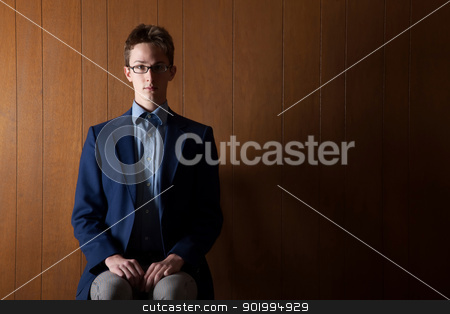 Young Man stock photo, Young Caucasian businessman sitting in room with paneling by Scott Griessel