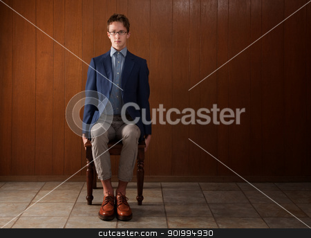 Young Stiff Man stock photo, Stiff young Caucasian man sitting on wooden chair by Scott Griessel