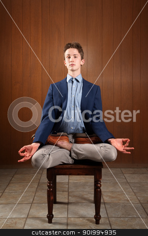 Young Man Meditating stock photo, Young Caucasian man meditating on a chair by Scott Griessel