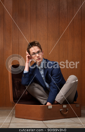 Man Sits In a Suitcase stock photo, Thinking young Caucasian man sits inside a suitcase by Scott Griessel