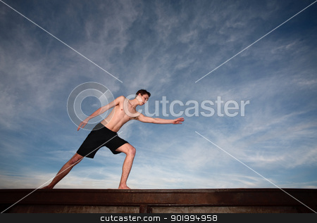 Young Man Exercises stock photo, Fit young Caucasian man exercising near a steel rail outside by Scott Griessel