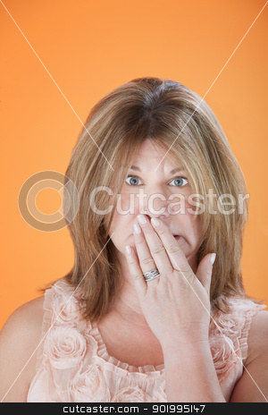 Worried Woman stock photo, Worried mature Caucasian woman with hand on mouth isolated on orange background by Scott Griessel