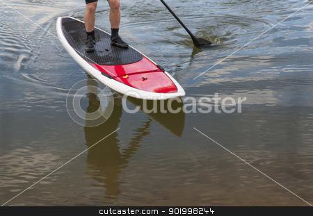 paddling stand up paddleboard stock photo, paddling stand up paddleboard on a lake - feet and legs of male paddler by Marek Uliasz