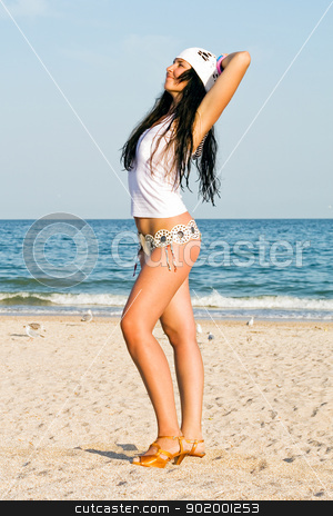 The young woman on sand at sea coast stock photo, The young woman on sand at sea coast by Sergii Sukhorukov
