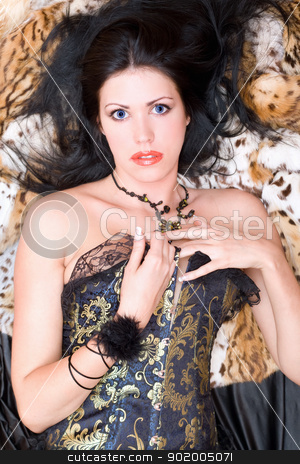 Sexy young brunette in a corset stock photo, Sexy young brunette in a corset posing on fur by Sergii Sukhorukov