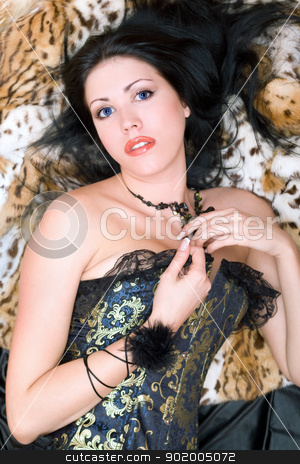 Pretty young brunette in a corset stock photo, Pretty young brunette in a corset posing on fur by Sergii Sukhorukov