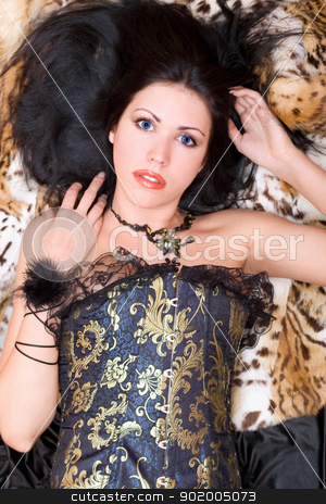 Attractive young brunette in a corset stock photo, Attractive young brunette in a corset posing on fur by Sergii Sukhorukov
