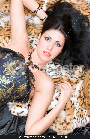 Portrait of a young brunette in a corset stock photo, Portrait of a young brunette in a corset posing on fur by Sergii Sukhorukov