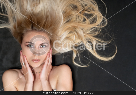 Portrait of attractive young blonde stock photo, Portrait of attractive young blonde lying on the gray fabric by Sergii Sukhorukov