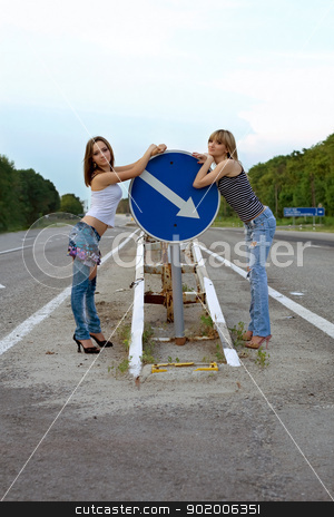 Two pretty girls stand on a road stock photo, Two pretty girls stand on a road near the sign by Sergii Sukhorukov