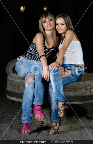 Two beautiful girls sitting on a stone stock photo, Two beautiful girls sitting on a stone bench by Sergii Sukhorukov