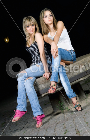 Two pretty girls sitting on a stone stock photo, Two pretty girls sitting on a stone bench by Sergii Sukhorukov