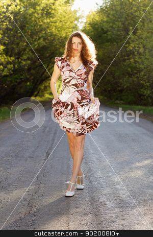 Beautiful woman walking on the road stock photo, Beautiful young woman walking on the road by Sergii Sukhorukov