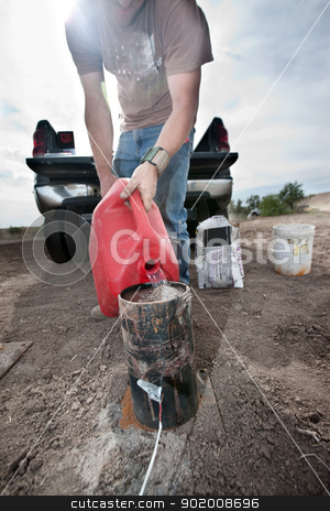 Pyrotechnic Worker Pouring Gasoline stock photo, Pyrotechnic expert pours gasoline into canister for controlled explosion by Scott Griessel