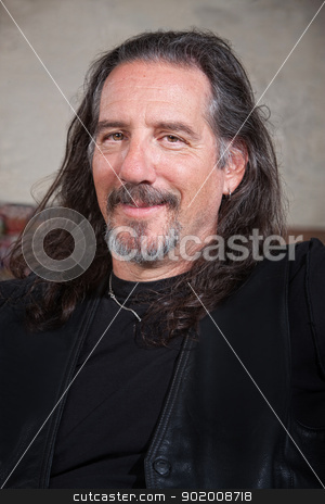 Smiling Male Biker Gang Member stock photo, Smiling long haired male with leather vest by Scott Griessel