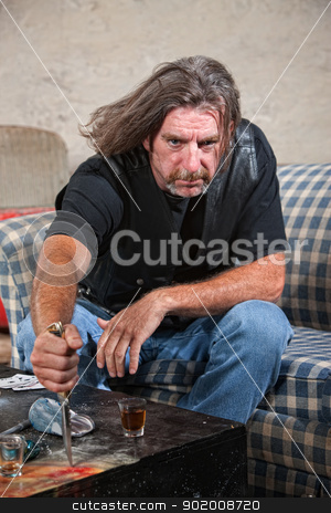 Angry Biker Gang Man with Dagger stock photo, Angry Caucasian male gang member with knife and shot glass on table by Scott Griessel