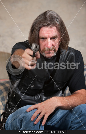 Man in Biker Gang Vest with Gun stock photo, Suspicious male in biker gang clothing aiming a pistol by Scott Griessel