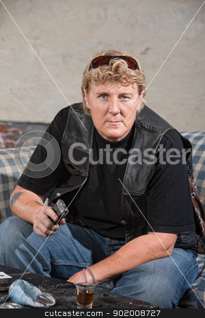 Tough Biker Woman Points Gun stock photo, Tough woman in leather jacket points a gun by Scott Griessel