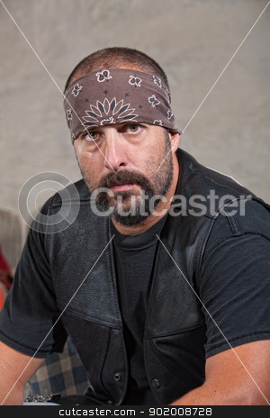Serious Bearded Man in Leather Vest stock photo, Serious bearded man with bandana and leather vest by Scott Griessel