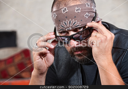 Biker with sunglasses and bandanna stock photo, Intimidating male biker in bandana looking over his sunglasses by Scott Griessel