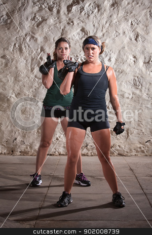 Women Doing Boot Camp Style Workout stock photo, Pretty woman working out and sweating while lifting kettle bell weights by Scott Griessel