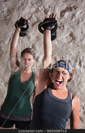 Instense Boot Camp Style Workout stock photo, Instense women shout as they push kettle bell weights up by Scott Griessel