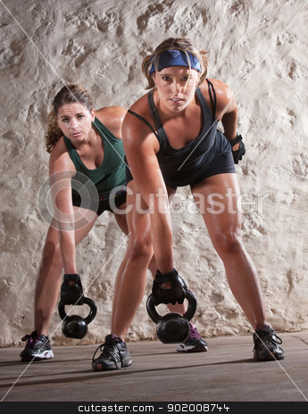Serious Boot Camp Style Workout stock photo, Serious pair of young women lifting weights during boot camp workout by Scott Griessel