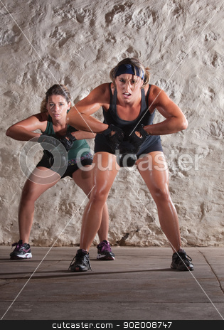 Two Women Struggle with Boot Camp Workout stock photo, Struggling young white women sweating and lifting weights by Scott Griessel