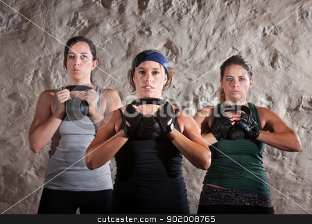 Friends Doing Boot Camp Style Workout stock photo, Serious women lifting kettlebells for boot camp style workout by Scott Griessel