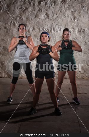 Boot Camp Workout Women stock photo, Three active females lifting large kettlebell weights by Scott Griessel
