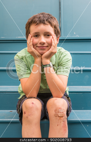 young boy with scrapes on knees stock photo, young boy in green on blue home steps by Ron Greer