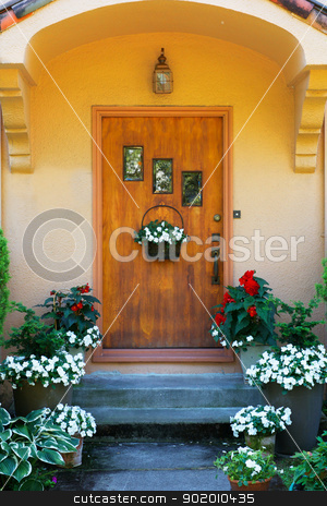 Weathered wood stained home door stock photo, Weathered wood stained home door with three windows and flowers by bobkeenan