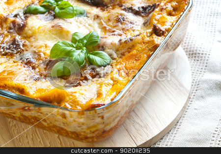 Lasagne stock photo, Freshly baked lasagne with fresh basil on top by Tiramisu Studio