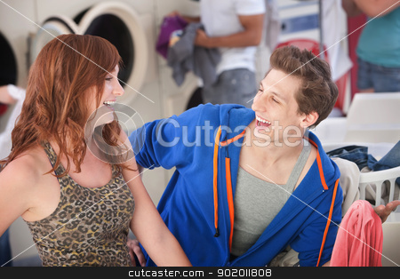 Happy Couple In Laundromat stock photo, Man and woman laugh about his white shirt turned pink by Scott Griessel