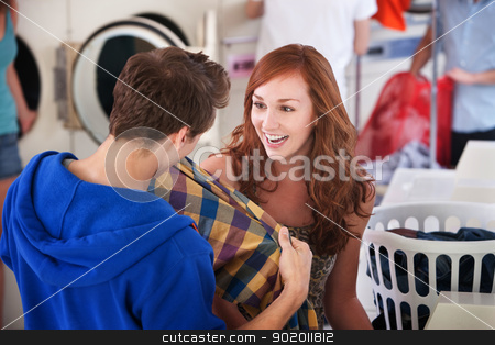 Smiling Young Lady stock photo, Young lady smiles as a man holds a shirt in the laundromat  by Scott Griessel