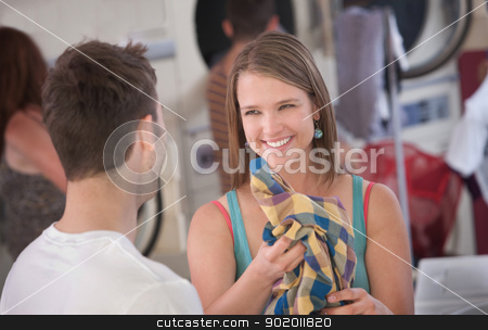 Flirting Woman in Laundromat stock photo, Beautiful smiling Caucasian woman holds a plaid shirt  by Scott Griessel