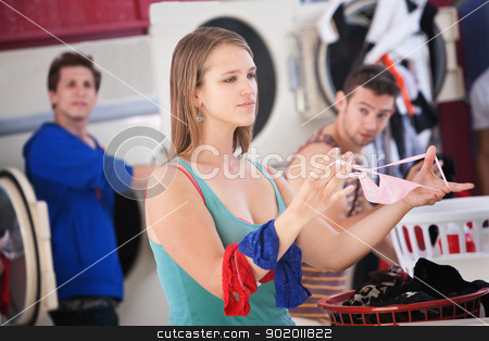 Folding Underwear stock photo, Beautiful young Caucasian lady folds underwear in the laundromat by Scott Griessel