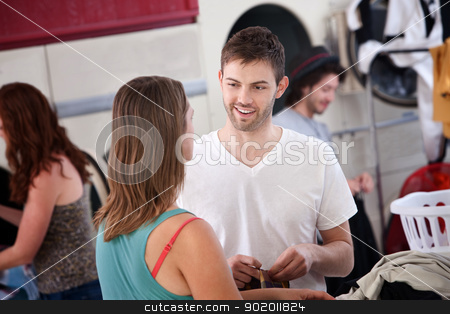Man Flirting In Laundromat stock photo, Handsome young Caucasian man talks with woman in laundromat by Scott Griessel