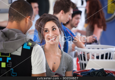 Happy Young Lady stock photo, Young Caucasian lady with boyfriend grins in laundromat by Scott Griessel