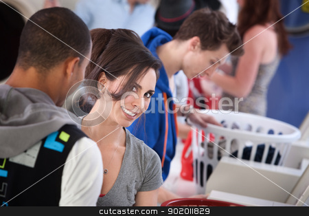 Beautiful Lady Smiling stock photo, Young woman with boyfriend smiles in laundromat by Scott Griessel