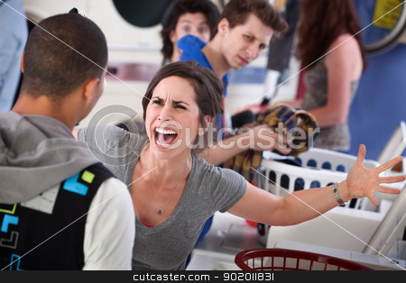 Mad in the Laundromat stock photo, Frustrated young woman yells at a man in the laundromat by Scott Griessel