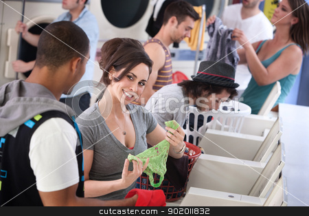 Laundromat Flirt stock photo, Woman holds panties and flirts with man in laundromat by Scott Griessel