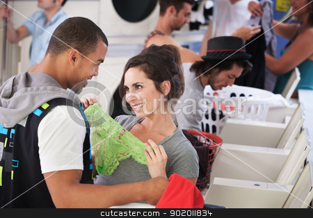 Romance In The Laundromat stock photo, Young lady holding underwear in front of man in laundromat by Scott Griessel