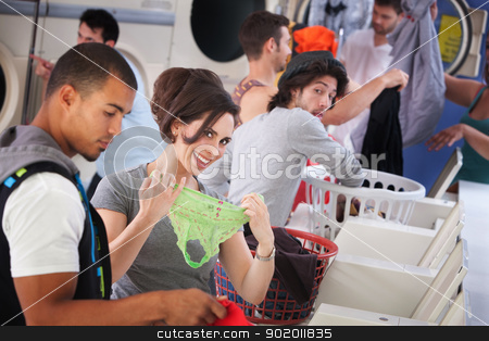 Smiling Woman Holding Underwear stock photo, Young woman shows disinterested man her panties in a laundromat by Scott Griessel