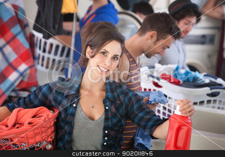 Smiling Woman In Laundromat stock photo, Beautiful Caucasian woman with clothes basket and detergent in the laundromat by Scott Griessel