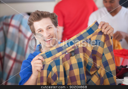 Grinning Man Holding Shirt stock photo, Grinning man holds a plaided shirt in laundromat by Scott Griessel