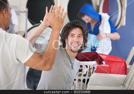Laundromat Friends stock photo, Two happy young friends high five in the laundromat by Scott Griessel