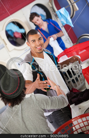 Friends Greeting Each Other stock photo, Two friends shake hands in the laundromat by Scott Griessel