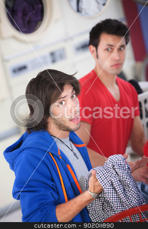 Unhappy Man  stock photo, Unhappy Latino man holds clothes in laundromat by Scott Griessel