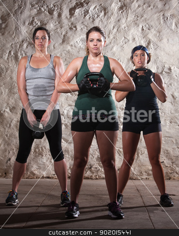Three Ladies in Boot Camp Workout stock photo, Three strong women lifting kettlebell weights during boot camp workout by Scott Griessel